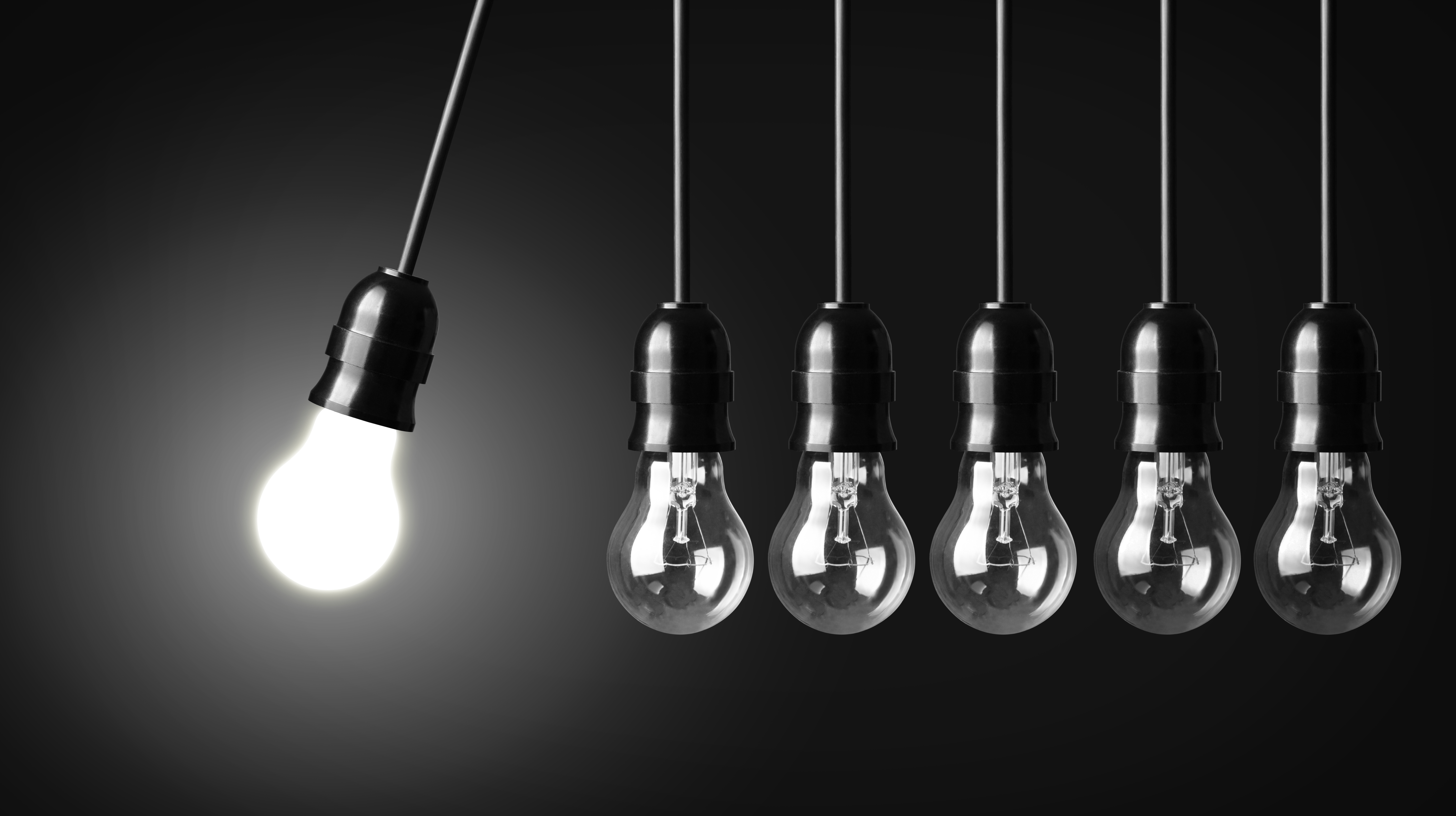 Idea concept on black. Perpetual motion with light bulbs